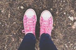 Entraîneurs de point de polka et jambes de femme dans des jeans Photographie stock