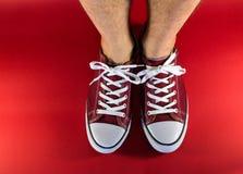 Entraîneurs rouges de toile et pieds humains Photographie stock