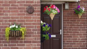 House door with hanging flower baskets stock photography