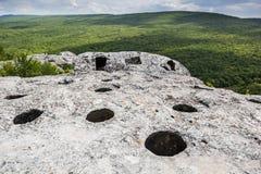 Entrada à caverna sobre a montanha, vista da floresta e o vale foto de stock royalty free