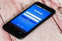 Entrada al facebook social de la red vía el teléfono móvil HTC Imagen de archivo libre de regalías