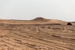 Entrada al gran desierto con los rastros del neumático y montaña de la arena en Dubai Imagenes de archivo