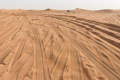 Entrada al gran desierto con los rastros del neumático y montaña de la arena en Dubai Imágenes de archivo libres de regalías