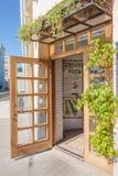 Entrada al restaurante acogedor, una puerta abierta, plantas colgantes Foto de archivo libre de regalías
