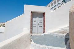 A entrada à casa cinzelou na rocha na borda do penhasco do caldera na cidade de Fira Thira (Santorini), Grécia Imagem de Stock