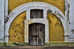 Entrada con el arco blanco y la pared amarilla brillante Fotos de archivo