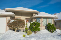 Entrada da casa luxuosa com jardim da frente na neve Imagem de Stock Royalty Free