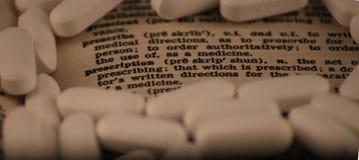 A entrada de dicionário para prescreve e prescrição cercada pelos comprimidos brancos Foto de Stock