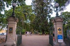 Entrada de los jardines botánicos de la ciudad con caminar abierto de las puertas y de la gente imagen de archivo