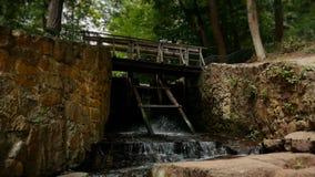 Entrada de madera vieja del agua con la cascada de la impulsión de cadena en la leva del deslizamiento del dren del lago almacen de video