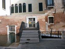 A entrada de uma casa de apartamento através do canal em Veneza Fotos de Stock Royalty Free