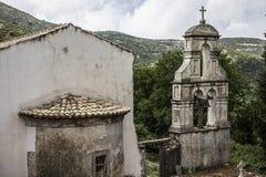 Entrada de una iglesia arruinada con las campanas viejas que cuelgan a la derecha del edificio La iglesia parece estar de épocas  Fotos de archivo libres de regalías