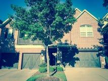 Entrada delantera filtrada de la imagen de la casa a estrenar con las puertas de madera del garaje cerca de Dallas, Tejas fotografía de archivo