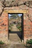 Entrada en pared de ladrillo en jardín de la cabaña Imagen de archivo libre de regalías