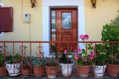 Entrada en una casa adornada con las plantas y las flores en los potes Foto de archivo