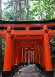 Entrada japonesa de la capilla con las columnas rojas y el fondo negro de los tejados fotografía de archivo