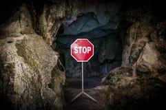 Entrada a la cueva oscura bloqueada con la muestra de la PARADA. Imagen de archivo