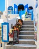 Entrada a la taberna griega tradicional, adornada con las verduras y la figura del cocinero Imagenes de archivo