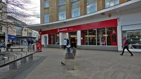 Entrada a la tienda de Vodafone, visión desde Broadmead, cuarto que hace compras en Bristol City Centre almacen de metraje de vídeo