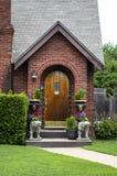 Entrada pequena bonito da casa de campo do tijolo decorada para o partido com os grânulos em estátuas do urso e em flores e em lu Fotografia de Stock Royalty Free