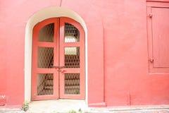 Entrada roja de la puerta del viejo estilo clásico al edificio Imágenes de archivo libres de regalías