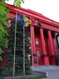 Entrada a una institución educativa con las columnas masivas que apoyan el tejado Con una asta de bandera delante de los pasos Imágenes de archivo libres de regalías