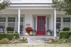 Entrada y pórtico a la casa bonita con las decoraciones del otoño y de Halloween y hojas de la caída que soplan en el viento - sú fotografía de archivo libre de regalías