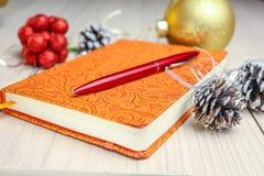 Entradas novas Lista de afazeres o ano da compra antes do Os brinquedos do Natal com festões encontram-se em uma tabela de madeir Foto de Stock Royalty Free