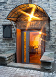 Entrance. An illuminated entrance with awning and a large glass door to a warmly lightened room Stock Image