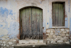 Entrance of an abandoned house with green door and window. Royalty Free Stock Photos