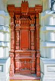 Entrance, antique, red, wooden door, decorated with rich and com. Plex carvings, located between two stone columns Stock Images