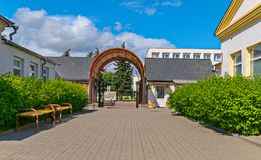 Entrance through the arch to a quiet area with green bushes and benches. For your design Royalty Free Stock Photo