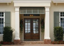 Entrance - Architectural Details. Architectural details to entrance of newly constructed home with green hurricane shutters,square columns, double glass doors royalty free stock images
