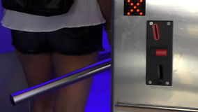 Entrance through automated barrier turnstile. Girl wearing jeans shorts inserting a coin or token into the slot at the entrance into the cinema, museum, venue