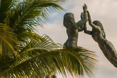 Entrance of the beach in Playa del Carmen, Mexico. Riviera Maya. Sculpture of a man and a woman in the form of an arch on the back. Ground of palm trees royalty free stock image