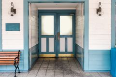 The entrance with blue door of wooden house. The entrance with closed door of wooden house within white and blue color, wooden chair placed in front and has two Royalty Free Stock Images