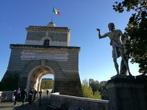 Entrance of Bridge Milvio, the oldest bridge in Rome. Italy. Entrance of Bridge Milvio, the oldest bridge in Rome, Italy. Italian flag. Statue on the right Royalty Free Stock Photography
