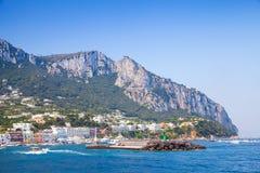 Entrance of Capri port, Italy. Boats go near breakwater Royalty Free Stock Photos
