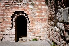 Entrance of a Castle - Round arch and brick walls. Spello, Umbria, Italy royalty free stock photo