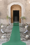 Entrance of a church decorated with pedestals of flowers and a g Royalty Free Stock Images