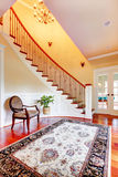Entrance with curved staircase and luxury rug with chair. Royalty Free Stock Photos