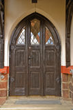 Entrance door in church. Wooden with glass and a canopy of grey colour Royalty Free Stock Images