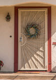 Entrance door. House entrance door behind the grid with summer wreath Stock Photography