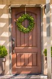 Entrance door. House entrance door with inside segment and summer wreath Royalty Free Stock Photo