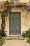 Entrance door. Old country house entrance door framed with wisteria Stock Image