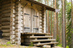 Entrance door and porch of log house in forest Royalty Free Stock Image