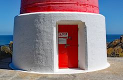 The entrance door of the red and white striped lighthouse at Cape Palliser on North Island, New Zealand. The light was built in royalty free stock image