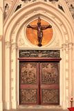 Entrance door to a church. Ornate carved entrance doors and entryway to a church or cathedral with a large crucifix above Royalty Free Stock Images
