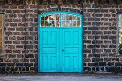 Entrance door to an old steel mill, building made of cinder stone. Turquoise entrance door to a very  old steel mill building, made of cinder stones Located in Stock Photo