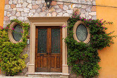 Entrance door with two round windows in the orange wall Stock Images